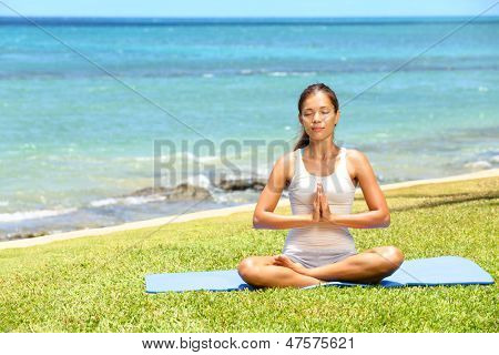 Yoga woman meditating woman relaxing by ocean sea doing the Sukhasana, easy pose. Woman in meditation in beautiful ocean landscape retreat. Meditation, yoga and relaxation concept.