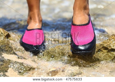 Water shoes in Pink neoprene on rocks in water on beach. Closeup detail of the feet of a woman wearing bright pink neoprene water shoes standing on rocks at the edge of the ocean.