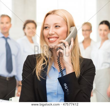bright picture of smiling woman with phone in office