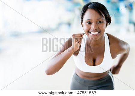 Competitive woman running at the gym looking happy