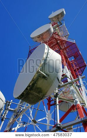 Big wireless communications antenna over clear blue sky