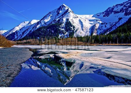 Beautiful Reflection of Snowy Mountain in Partially Frozen Lake in Alaska.