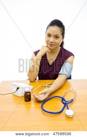 Young adult woman happy with her self blood pressure test (Selective focus at woman)