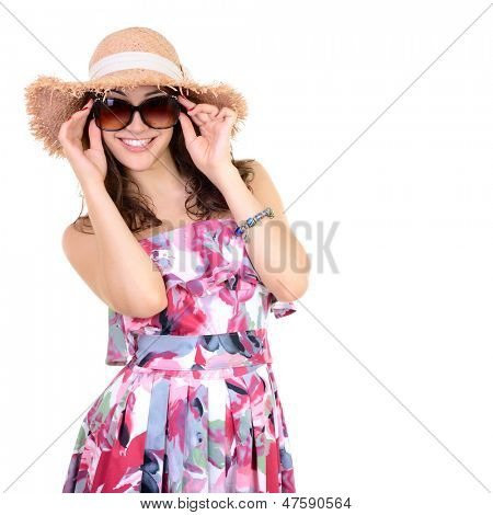 Beautiful cheerful confident young woman in sunglasses and straw hat, over a white background