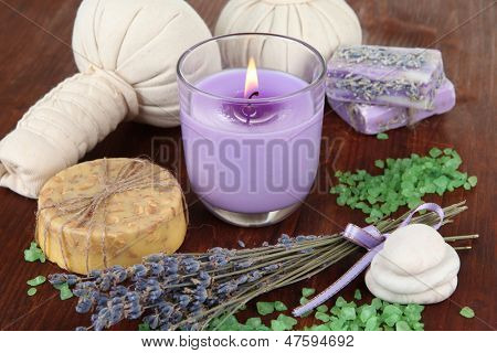 Still life with lavender candle, soap, massage balls, bottles,  soap and fresh lavender, on wooden  table on wooden background
