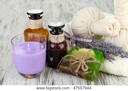 Still life with lavender candle, soap, massage balls, bottles,  soap and fresh lavender, on wooden background