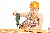 foto of hand drill  - Female carpenter with helmet at work using hand drilling machine isolated on white background - JPG