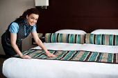 foto of housekeeping  - Elegant housekeeping lady adding final touches to bedroom before customer arrival - JPG
