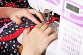 stock photo of sewing  - sewer sews clothes on sewing machine close up - JPG