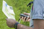 image of gps  - Man holding a GPS receiver and plan in his hand - JPG