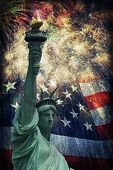 stock photo of veterans  - Composite photo of the statue of Liberty with a flag and fireworks in the background - JPG