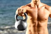 Crossfit fitness man training with kettlebells outtside. Kettlebell closeup of fit male sport athlet