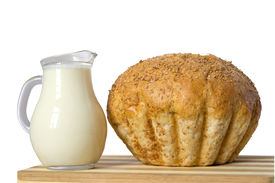 foto of milkman  - Milk in a milkman and a loaf of bread are on the cutting board - JPG