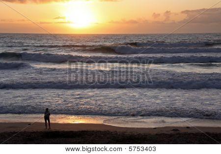 Una silueta dama viendo la puesta de sol, la tierra sea scape en el famoso surf playa de la bahía de Fistral, C