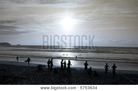 Silhouettes of swimmers / surfers and people watching the sun set and sea scape at the famous surfin