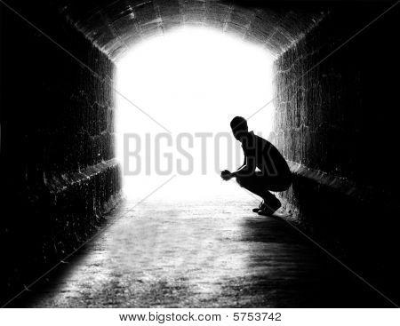 Silueta humana sentada en retroiluminada en la salida del túnel