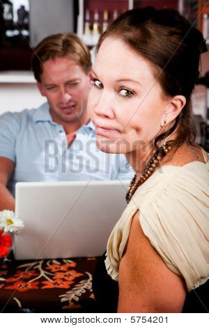 Man Using Laptop Ignoring His Date In Coffee House