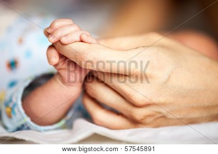 Newborn baby holding mother's hand