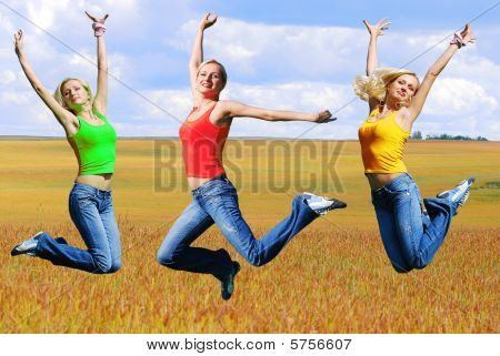 Beautiful athletic woman jumping on a green meadow