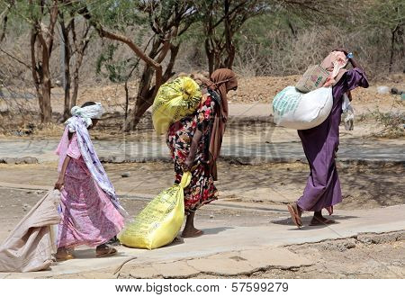 African Women Carrying The Help They Receive To Their Homes