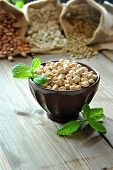 image of bengal-gram  - raw chickpeas in a brown bowl with herbs - JPG