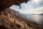 stock photo of cave woman  - Rock climber climbing at the rock at sunset - JPG