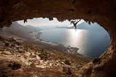 stock photo of cave woman  - Family rock climber against picturesque view of Telendos Island at sunset - JPG