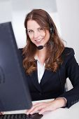 stock photo of receptionist  - Smiling receptionist or call centre worker sitting typing at a computer while speaking into a headset with a microphone - JPG