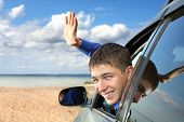pic of goodbye  - happy young man sitting in the car and wave goodbye - JPG