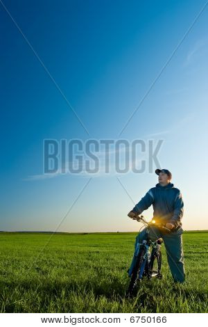 Man On Bike In The Green Field