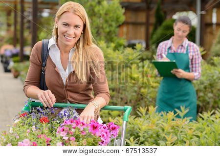 Woman shopping for flowers in garden center employee doing inventory