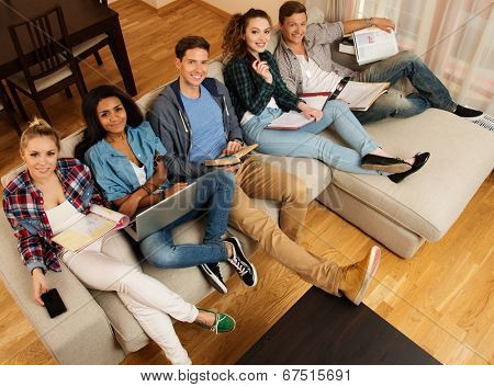Group of multi ethnic young students preparing for exams in home interior