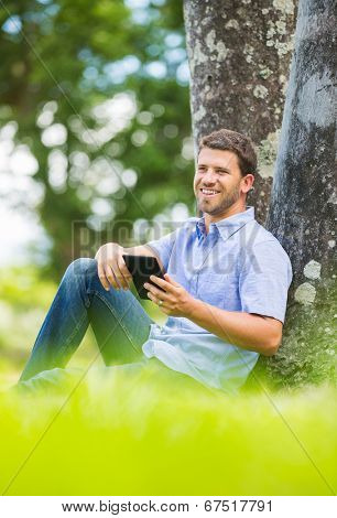 Young man reading E-Book outside in park