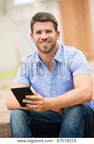 Young man reading E-book outside on steps