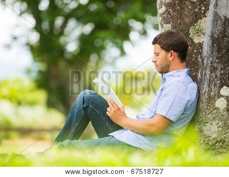 Man reading book in park, sitting under a tree. Relaxing outdoors reading.