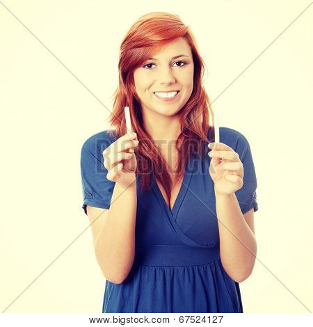 Young woman holding cigarette and electronic cigarette.