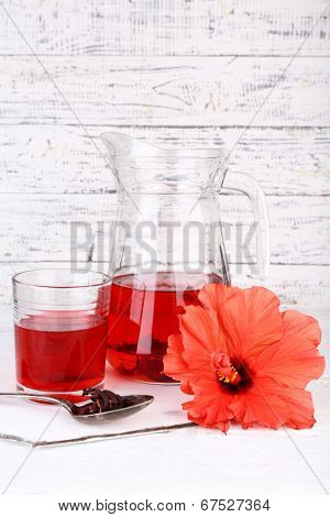 Cold hibiscus tea in glass jug with hibiscus flower on wooden background