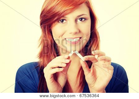 Young happy woman breaking cigarette, over white background