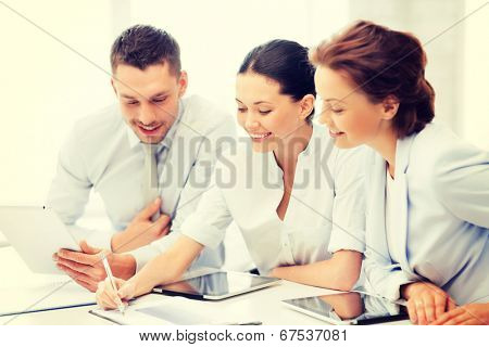 friendly business team with tablet pcs having discussion in office