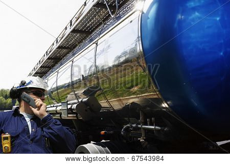 industry worker, driver talking in phone, large fuel-truck in the background