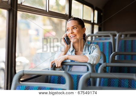 beautiful female commuter talking on cell phone while taking bus to work
