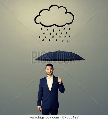 smiley businessman with black umbrella standing under drawing storm cloud. photo over grey background