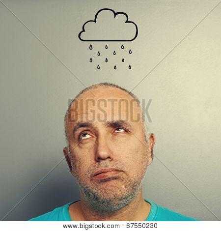 portrait of stressed senior man with drawing storm cloud over grey background