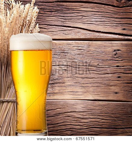 Ears of wheat & beer glass on old wooden table.
