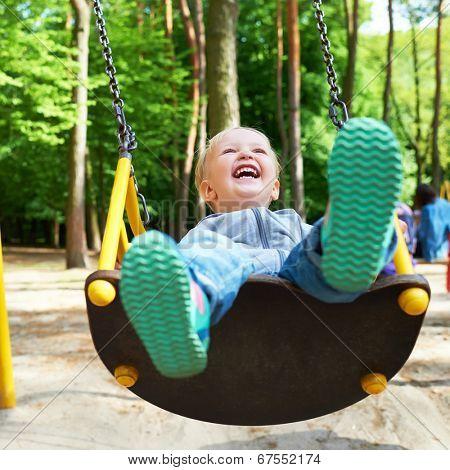 Happy little blond boy having fun on a swing in a summer park.