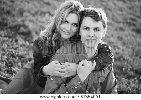 Happy young couple sitting in a park. Black and white photo