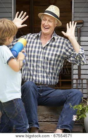 Grandfather and grandson playing in garden