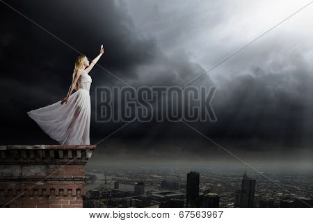 Young woman in white long dress on top of building