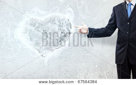 Businessman pointing at stone in shape of heart