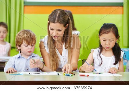 Children and educator painting in kindergarten with brushes on paper